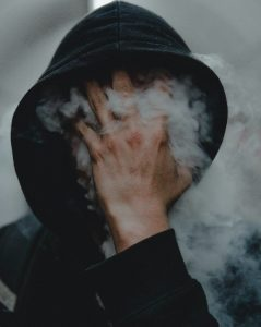 a man with his hand in front of his face, covered in smoke to depict defiance regarding quitting substances