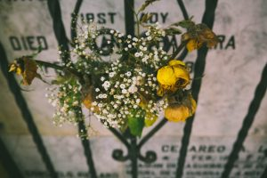 flowers on a fence in memorium to remind readers of how stressful grief can be in sobriety