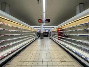 a picture of empty grocery store shelves to represent the pandemic and its stress