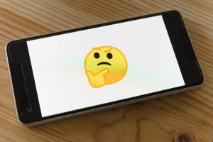 a picture of a phone with a thinking emoji to underscore the idea that you can't think your way into sobriety